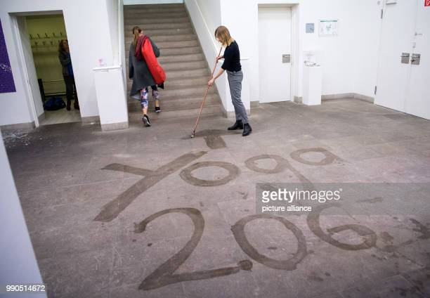 A woman carriying a yoga mat goes to a yoga course past a museum's employee who writes 'Yoga 2 OG' on the ground with water at the Gallery Stadt...