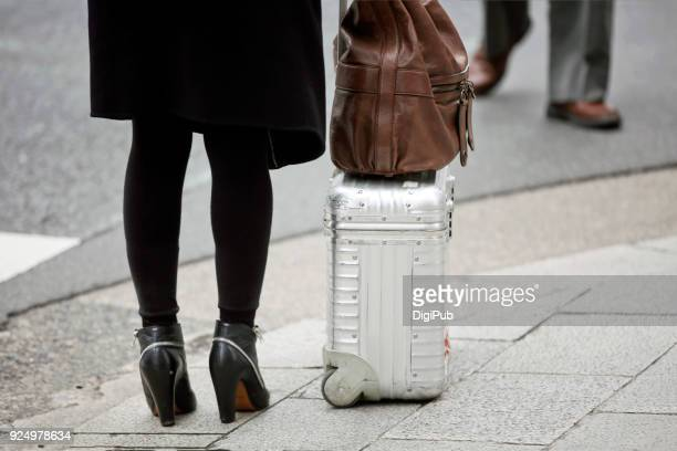 woman carry aluminum suitcase and leather bag - タイツ ストックフォトと画像