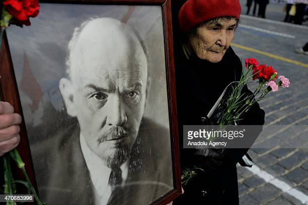 A woman carry flowers at Moscow's Red Square to leave them on the Soviet founder Vladimir Lenin's Mausoleum on Lenin's birthday April 22 2015 in...