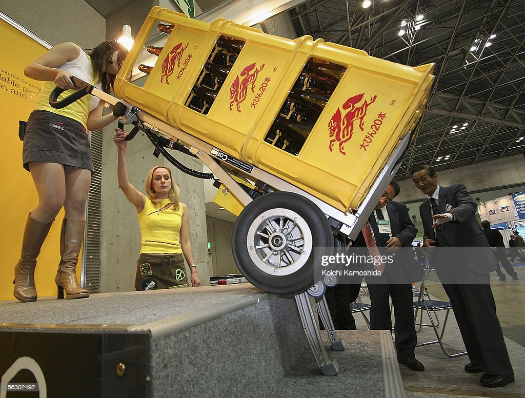 Woman carry heavy crates with the support of 'Carin' during the 2005 International Robot Exhibition on November 30, 2005 in Tokyo, Japan. With the assistance of an electronic Carin, a person can carrying up to 310kg with little effort. The Exhibition is on until December 3.