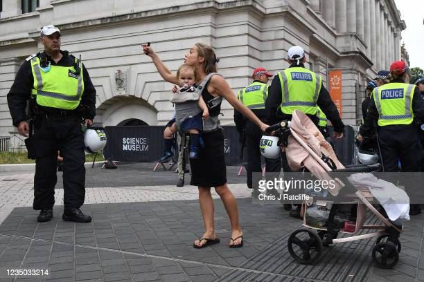 Woman carrying a baby argues with the police as she takes part in an anti-vaccination protest outside the Science museum on September 3, 2021 in...