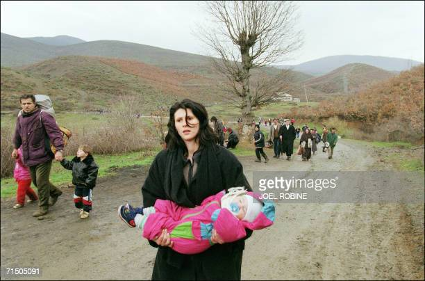 A woman carrying a baby arrives in Albania 03 April 1999 with fellow ethnic Albanian refugees fleeing Serb repression in Kosovo via the tiny border...
