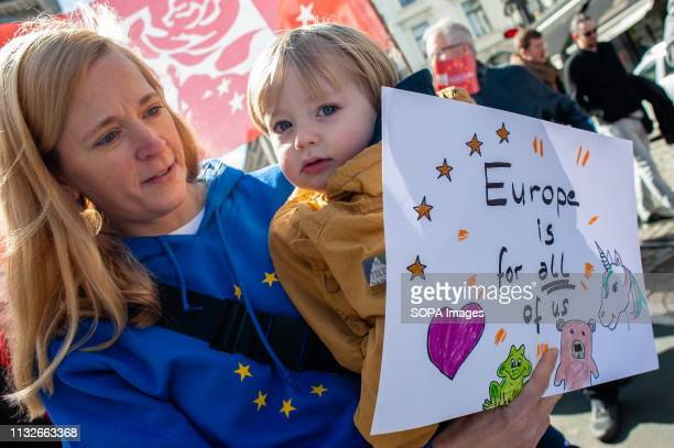 A woman carrying a baby is seen holding a placard during the protest A day before the anniversary of the founding Treaty of the European Union...