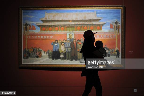 TOPSHOT A woman carrying a baby visits an exhibition at the China National Art Museum in Beijing on April 5 2016 / AFP / WANG ZHAO / RESTRICTED TO...