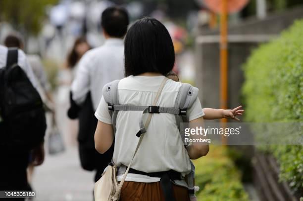 A woman carrying a baby walks along a sidewalk in Kawasaki Kanagawa Prefecture Japan on Tuesday Sept 18 2018 Japan's population of 127 million...