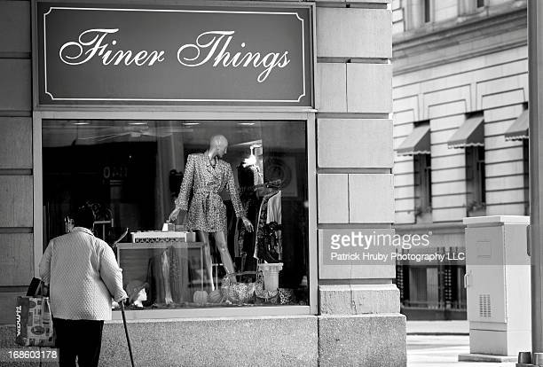 """Woman carrying a bag from a discount retailer stands under a juxtaposing sign that reads """"Finer Things""""."""
