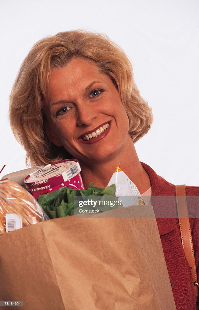 Woman carrying a bag of groceries : Stockfoto