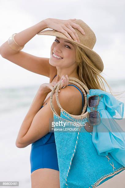 woman carrying a bag on the beach - woman carrying tote bag stock photos and pictures