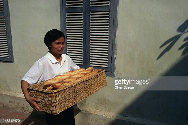 Woman carrying a basket of fresh baguettes.