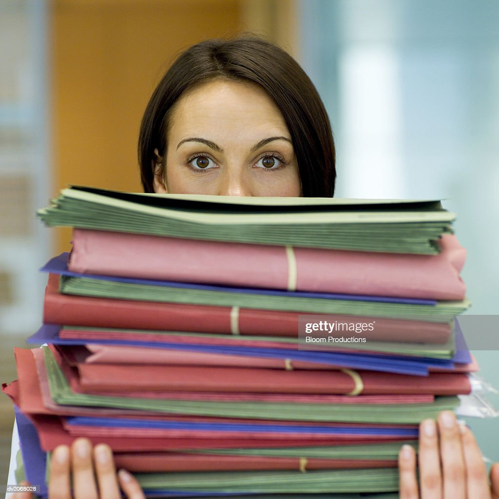 Woman Carrying a Big Pile of Folders, Her Face Obscured : Stock Photo