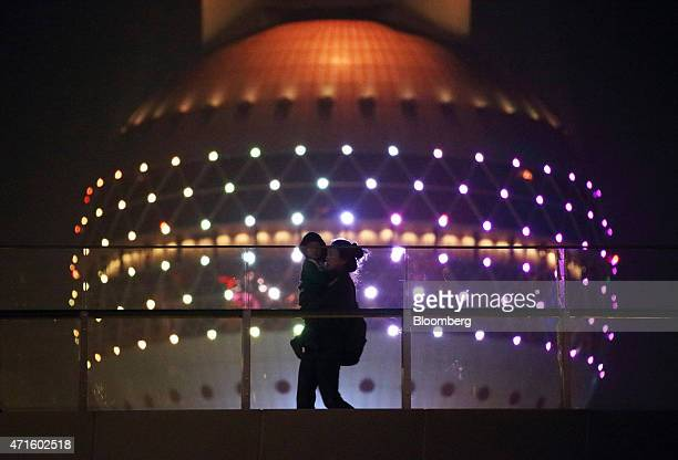 A woman carrying a boy walks past the Oriental Pearl Radio TV Tower in the Lujiazui district of Shanghai China on Friday April 24 2015 Yuan forwards...