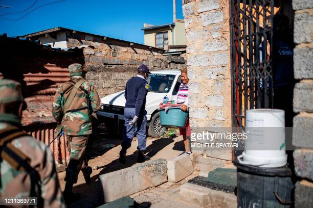 Woman carrying a bucket looks on a mixed patrol of South African National Defence Force and South African Police Service in Alexandra township in...
