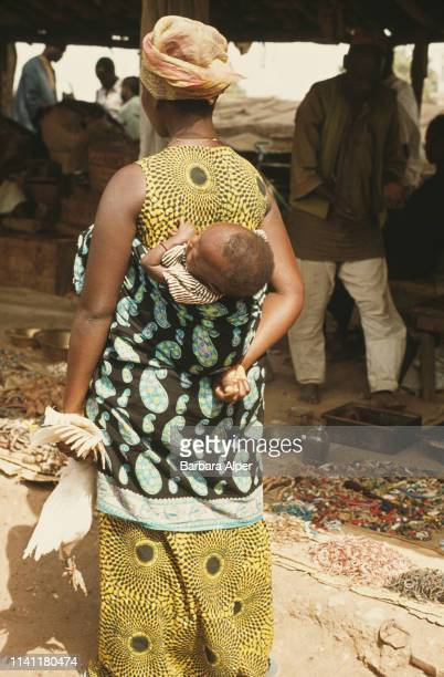 A woman carrying a chicken with her baby in Abidjan Ivory Coast February 1975