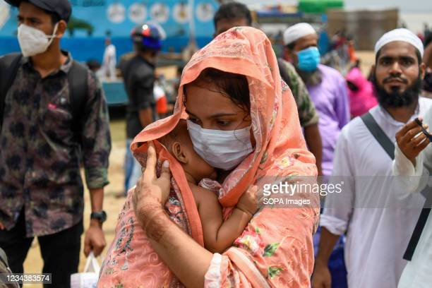 Woman carrying a child returns to her work area in Dhaka after government relaxed the lockdown restrictions. Thousands of Bangladeshi garment workers...