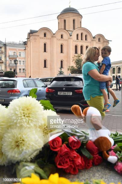 A woman carrying a child walk past flowers and candles laid in front of the Dutch embassy in Kiev on July 17 to remember those killed on flight MH17...