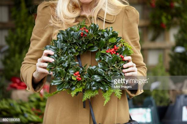 a woman carrying a decorated wreath of holly and evergreen leaves. - wreath stock pictures, royalty-free photos & images