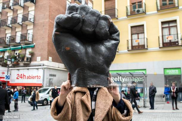 A woman carrying a fist sculpture as a part of demonstration during the first women strike ever in Spain for the International Women's Day