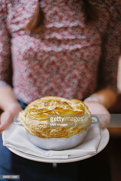 A woman carrying a fresh baked pastry topped pie on a plate.