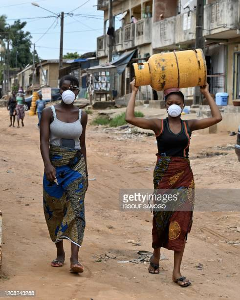 A woman carrying a gas bottle on her head while wearing a mask as a preventive measure against the spread of the COVID19 Coronavirusis walks through...