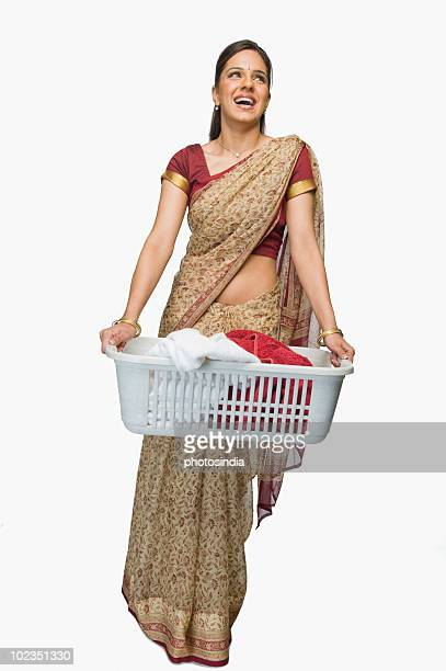 Woman carrying a laundry basket and day dreaming