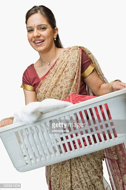Woman carrying a laundry basket and smiling