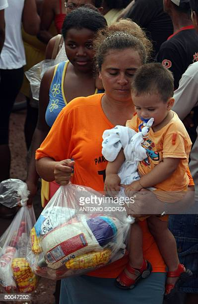 A woman carrying a little boy leaves the line after receiving a basket of basic food at the entrance of the farm of Tailandia's mayor on February 28...