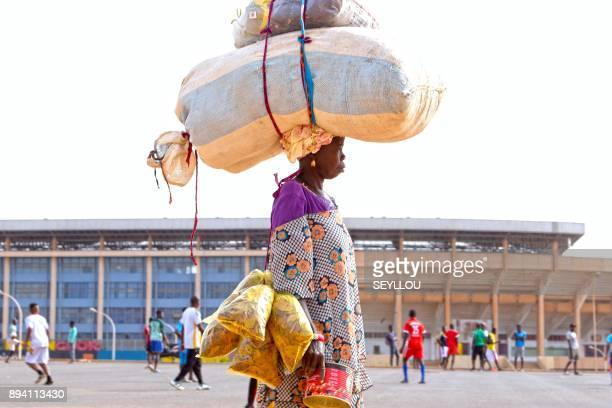TOPSHOT A woman carrying a load on her head walks past young men playing football in front of Leopold Sedar Senghor Stadium in Dakar on December 17...