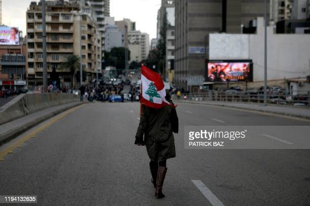 Woman carrying a national flag walks toward Lebanese demonstrators blocking the main bridge linking the western and eastern sides of the capital...