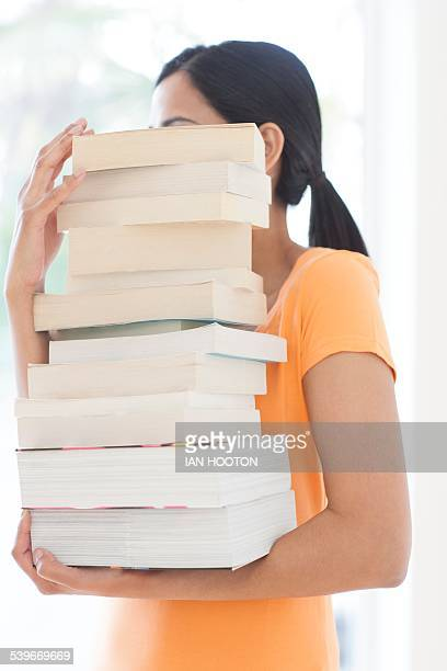 woman carrying a pile of books - obscured face stock photos and pictures