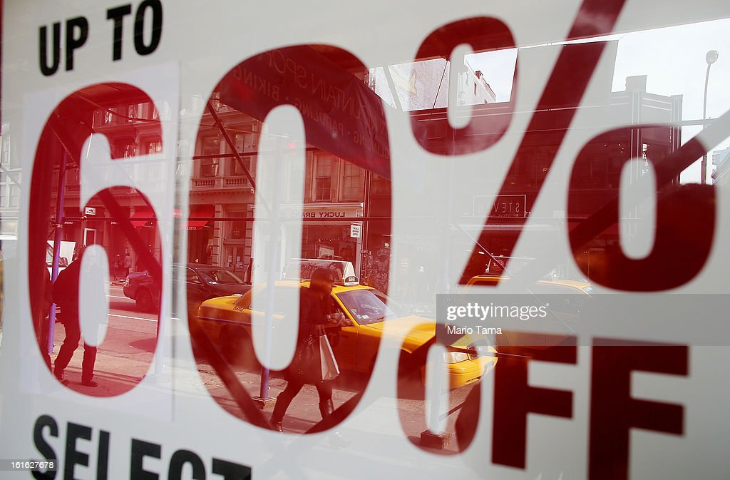 A woman carrying a shopping bag on Broadway in Manhattan is reflected in a window with a sale sign on February 13, 2013 in New York City. The Commerce Department reported that retail sales were only up slightly in January following tax increases and high gas prices.