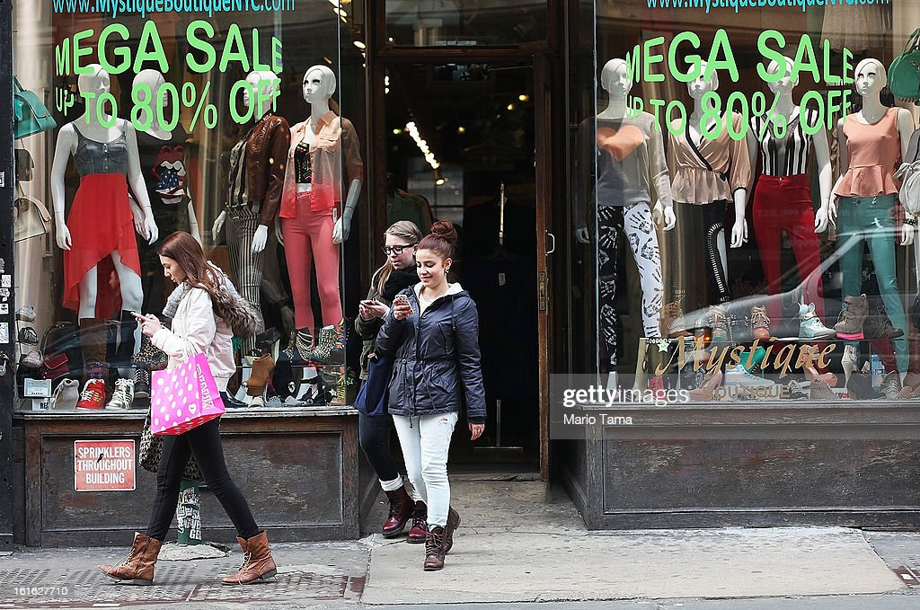 A woman carrying a shopping bag walks past a store advertising sales on Broadway in Manhattan on February 13, 2013 in New York City. The Commerce Department reported that retail sales were only up slightly in January following tax increases and high gas prices.