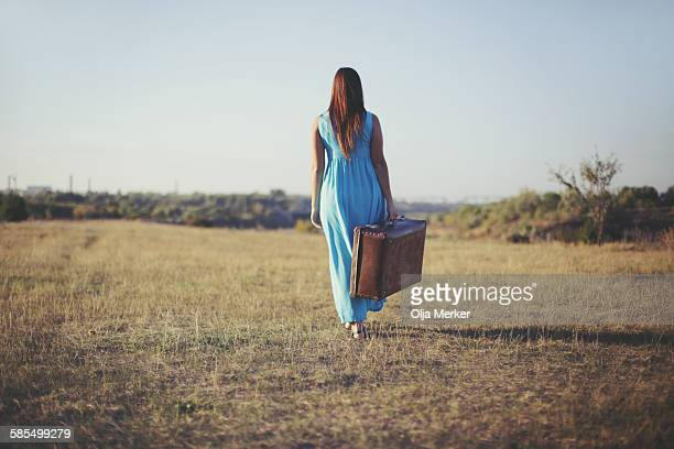 woman carrying a suitcase - long dress stock pictures, royalty-free photos & images