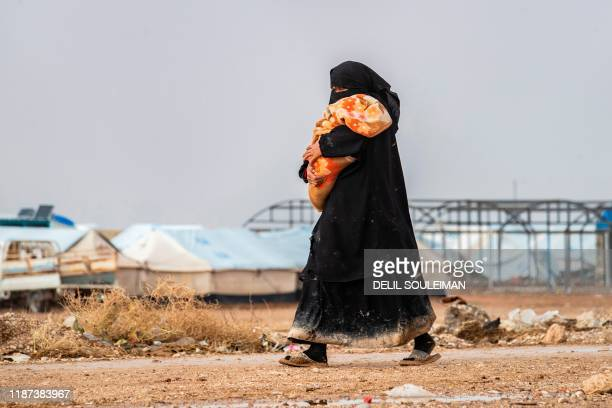 Woman carrying a toddler walks at the Kurdish-run al-Hol camp for the displaced where families of Islamic State foreign fighters are held, in the...