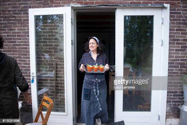 Woman carrying a tray of tomato soup outdoors