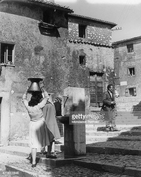 A woman carrying a vessel full of water near the house of Enrica Di Domenicantonio jury member of the Fenaroli trial Castel San Pietro Romano 21st...