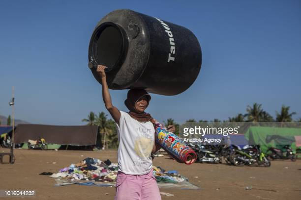 A woman carrying a water reservoir and bed mat is seen as volunteers distribute aid in the form of food and clothing at a temporary shelter in Lombok...