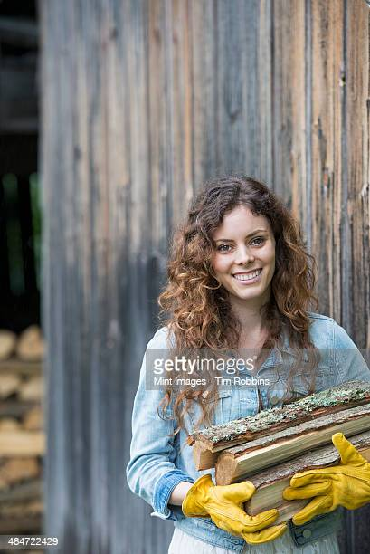 A woman carrying an armful of firewood from the logstore on the farm.