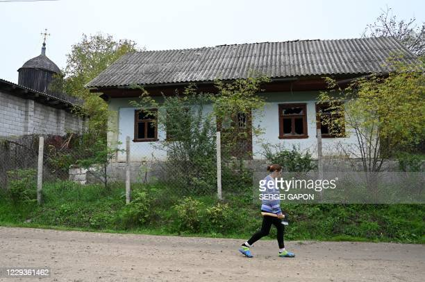 Woman carrying an ax walks past an abandoned house in the village of Vorniceni, some 40 km northwest of Chisinau, on October 30, 2020.