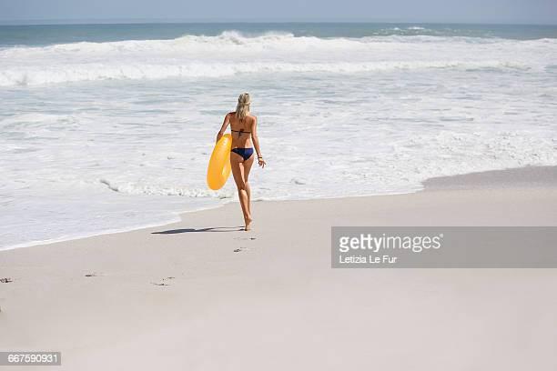 woman carrying an inflatable ring on the beach - femme blonde en maillot de bain vue de dos photos et images de collection