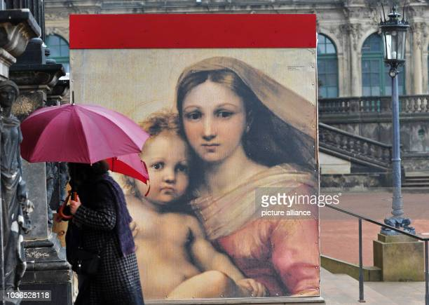 Woman carrying an umbrella passes a replica of Raphael's Sistine Madonna in front of an art gallery at the Zwinger in Dresden, Germany, 08 April...