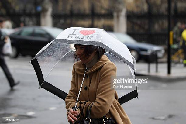 A woman carrying an umbrella that reads I love rain walks across Parliament Square on November 8 2010 in London England Forecasters have predicted...