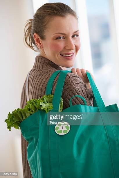 woman carrying bag of groceries - environmental issues imagens e fotografias de stock