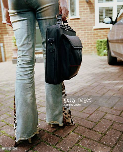Woman carrying bag up driveway, low section