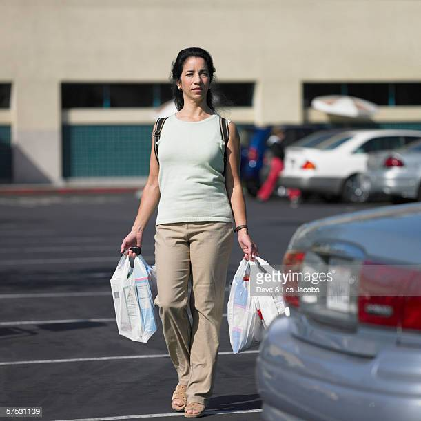 Woman carrying bags of groceries through parking lot