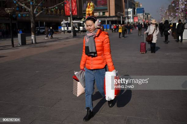 A woman carrying bags walks along a business street in Beijing on January 18 2018 Local government debt expanded again in China last year despite...