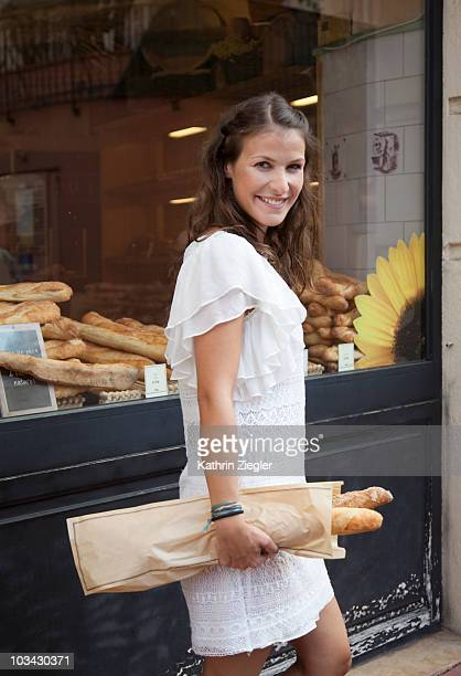 woman carrying baguettes - baguette stock pictures, royalty-free photos & images