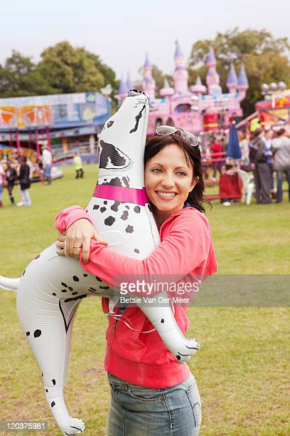 Woman carrying balloon in shape of dog.
