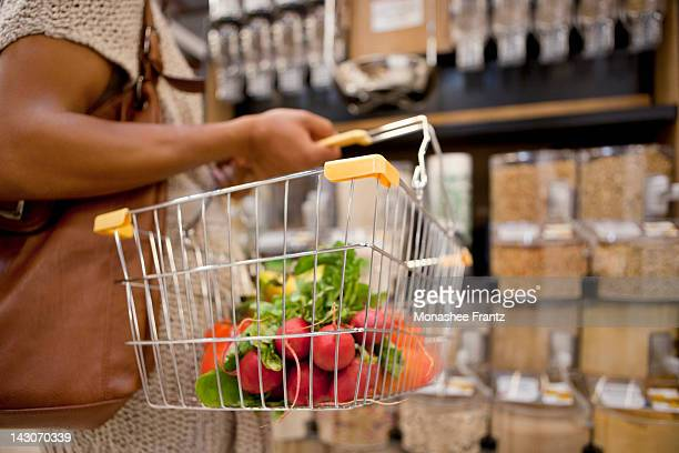 Woman carrying basket in supermarket