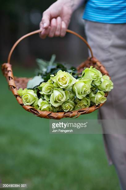 Woman carrying basket of flowers, close-up