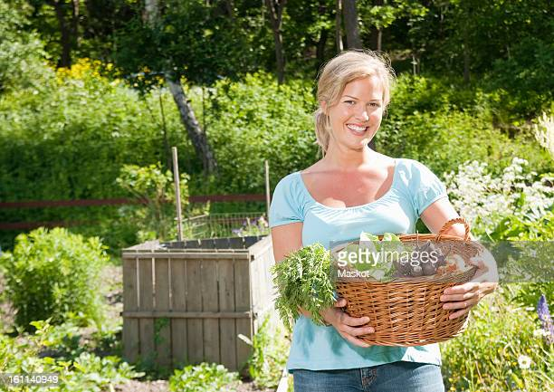 Woman carrying basket with vegetables